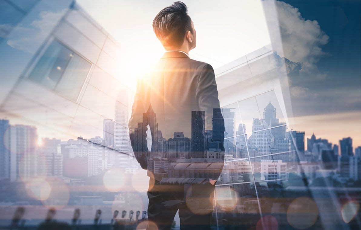 Image of a businessman looking upward and superimposed upon a city skyline