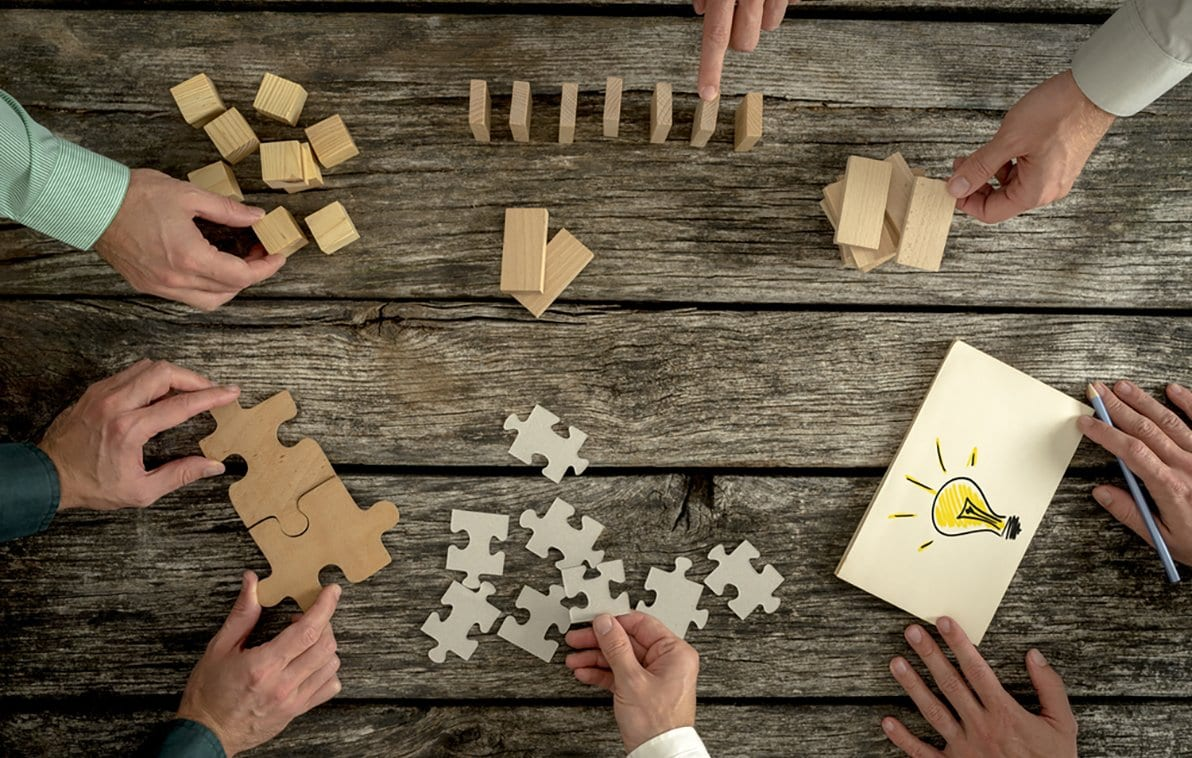 Overhead photo of several peoples hands assembling various puzzle pieces
